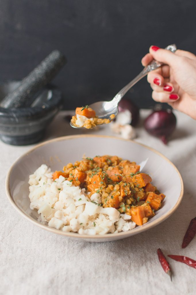 This vegan curry recipe made of sweet potatoes and red lentil, is easy and quick to make, spicy and very healthy. Served with cauliflower rice it is low-carb and keto-friendly as well. #lowcarbrecipes #vegandinnerideas #curryrecipes #cauliflowerrice