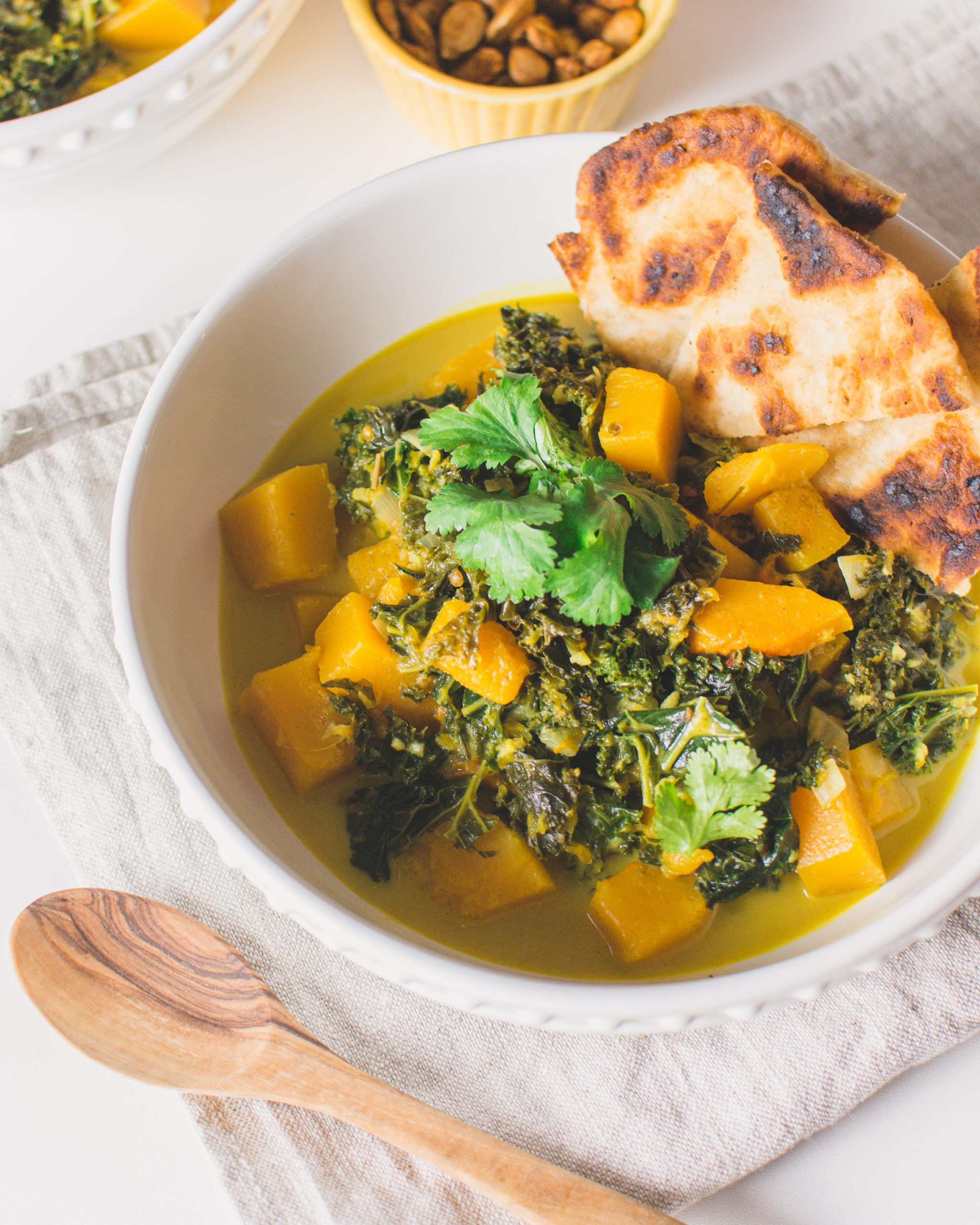 Vegan Pumpkin Kale Curry - Butternut Squash and Kale make the best vegan curry! It's easy to make, healthy and a comfort food. You can make the pumpkin kale curry in one pot and make it for lunch or dinner. Serve with homemade naan bread and enjoy this delicious recipe! #vegancurry #pumpkincurry #kalerecipe #veganrecipe #vegetarian #coconutmilk #kale