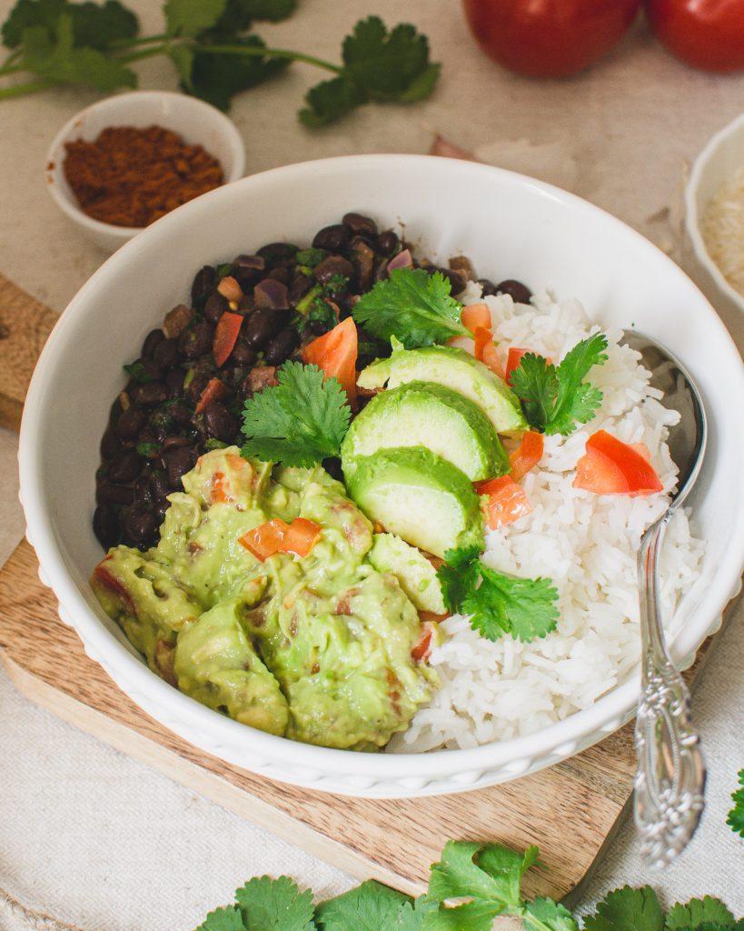 Dieses vegane Burrito Bowl ist einfach, gesund und so lecker! Das Rezept besteht aus Reis, würzigen schwarzen Bohnen mit Koriander und frischer Guacamole. Es ist ein schnelles mexikanisches Rezept auf pflanzlicher Basis, das sich perfekt zum Mittag- oder Abendessen eignet! #vegan #burritobowl #veganburritobowl #veganerezepte #veganesmittag #veganerezeptideen